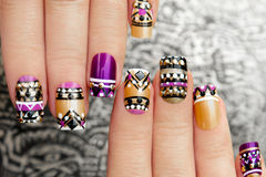 Manicure with colorful ethnic design. Manicure with colorful ethnic design with rhinestones on female hand close up on colorful background stock image