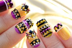 Manicure with colorful ethnic design. With rhinestones on female hand close up on colorful background stock photo
