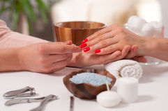 Manicure concept. Beautiful woman`s hand wiith red nails in the spa. Relaxing day at beauty salon. Manicurist master makes manicure on woman`s hand.  Hand care Stock Images