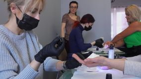 Manicure courses student concentrates on gel coating. Student of manicure courses concentrates on gel coating. Teacher observes from afar stock video footage