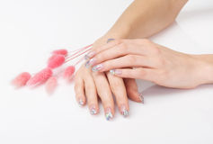 Manicure with crystalline flecks. And pink decoration isolated on white stock image