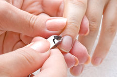 Manicure, cuticle cut. Nail salon, manicure applying - cuticle cut using special scissors stock photo