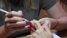 Manicure die een gradiënt met een borstel op de spijker van de cliëntduim creëren stock videobeelden