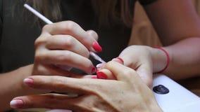 Manicure die een gradiënt met een borstel op de spijker van de cliëntduim creëren stock video