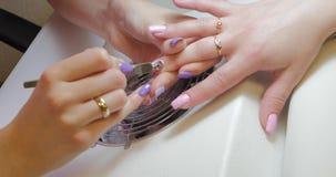 Manicure die opperhuidopdringer gebruiken om laatste correcties in gelmanicure te maken stock videobeelden