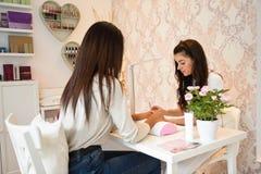 Manicure el cuidado del clavo para el cliente que se sienta en una tabla en el offi fotos de archivo libres de regalías