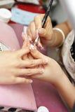 Manicure el proceso en la mano femenina Imagen de archivo