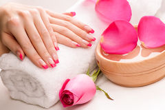 Manicure with fragrant rose petals and towel. Spa Royalty Free Stock Photo