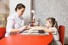 Manicure for girl. Caucasian female manicurist makes manicure for little girl sitting opposite her at the red desk. Horizontal shot Stock Photography