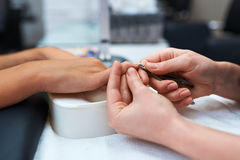 Manicure and hand the client, which are cut cuticle Royalty Free Stock Photo