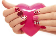 Manicure with hearts. Manicure with rhinestones in the shape of hearts and pink balls on white and red nail Polish on a white background Stock Photography