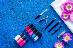 Manicure i skönhetsalong Hjälpmedel för manikyr, spikar polermedel och handdukar på blå skrivbords- siktscopyspace royaltyfri foto