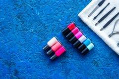 Manicure i skönhetsalong Hjälpmedel för manikyr, spikar polermedel och handdukar på blå skrivbords- siktscopyspace Fotografering för Bildbyråer
