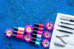 Manicure i skönhetsalong Hjälpmedel för manikyr, spikar polermedel och handdukar på blå skrivbords- siktscopyspace Royaltyfria Bilder