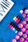 Manicure i skönhetsalong Hjälpmedel för manikyr, spikar polermedel och handdukar på blå skrivbords- siktscopyspace Royaltyfri Bild