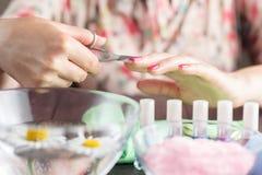 Manicure la aplicación, cortando la cutícula con las tijeras Fotografía de archivo libre de regalías