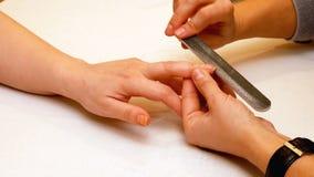 Manicure la peinture et les ongles de polissage dans le salon de station thermale Photo libre de droits