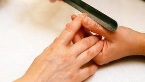 Manicure la peinture et les ongles de polissage dans le salon de station thermale Photo stock