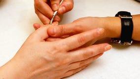 Manicure la peinture et les ongles de polissage dans le salon de station thermale Photos libres de droits