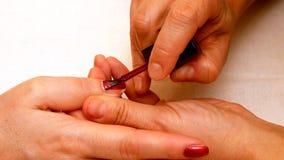 Manicure la peinture et les ongles de polissage dans le salon de station thermale Image libre de droits