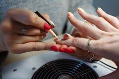 Manicure le maître, doigt orange de vernis à ongles de gel de couleur Images stock