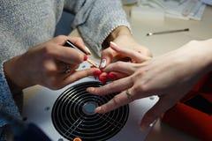 Manicure le maître, doigt orange de vernis à ongles de gel de couleur Photo stock