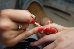 Manicure le maître, doigt orange de vernis à ongles de gel de couleur Image stock