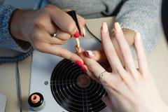 Manicure le maître, doigt orange de vernis à ongles de gel de couleur Photos libres de droits