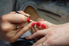 Manicure le maître, doigt orange de vernis à ongles de gel de couleur Images libres de droits