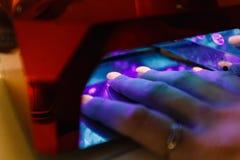 Manicure le maître, doigt orange de vernis à ongles de gel de couleur Photographie stock libre de droits