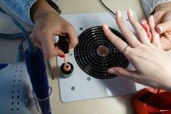 Manicure le maître, doigt orange de vernis à ongles de gel de couleur Photo libre de droits