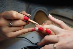 Manicure le maître, doigt orange de vernis à ongles de gel de couleur dans le sel d'ongle Images stock