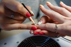 Manicure le maître, doigt orange de vernis à ongles de gel de couleur dans le sel d'ongle Photos stock
