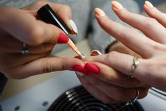 Manicure le maître, doigt orange de vernis à ongles de gel de couleur dans le sel d'ongle Image libre de droits