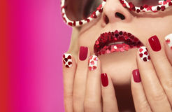 Manicure and lips with hearts. Of different shapes and colors on the girl with the glasses Stock Photography