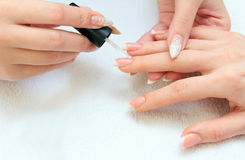 Manicure making - female hands, covering enamel Stock Images