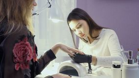 Manicure master covers nails with lacquer. Young attractive manicure master and client are in the cabinet. Young pretty lady wearing black gloves covers woman`s stock video