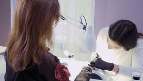 Manicure master covers nails with lacquer a young girl. Young attractive manicure master and client are in the cabinet. Young pretty lady wearing black gloves stock video footage