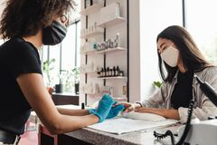 Free Manicure Master In Protective Medical Mask In Beauty Salon. African American Girl In Gloves Doing Nail Procedure Royalty Free Stock Photography - 194938527