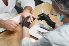 The manicure master cleans the nail from the cuticle. stock images