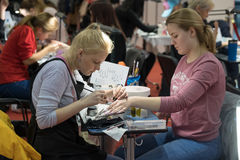 Manicure master works with client. Moscow, Russia - March 3, 2017: Competition of manicure at the Esthetic Life Exhibition Royalty Free Stock Photography