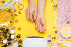 Manicure - means for creating, gel polishes, all for nail care, beauty concept, care. On a yellow background, a woman receives a. Manicure of n,ails. Service stock photo