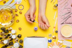 Manicure - means for creating, gel polishes, all for nail care, beauty concept, care. On a yellow background, a woman receives a. Manicure of nails. Service set royalty free stock photos