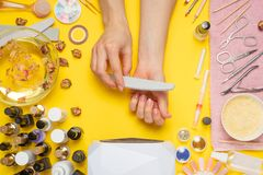Manicure - means for creating, gel polishes, all for nail care, beauty concept, care. On a yellow background, a woman receives a. Manicure of nails. Service set royalty free stock photography