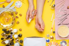 Manicure - means for creating, gel polishes, all for nail care, beauty concept, care. On a yellow background, a woman receives a. Manicure of nails. Service set stock images