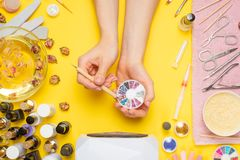 Manicure - means for creating, gel polishes, all for nail care, beauty concept, care. On a yellow background, a woman receives a. Manicure of nails. Service set royalty free stock photo