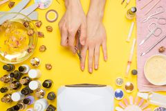 Manicure - means for creating, gel polishes, all for nail care, beauty concept, care. On a yellow background, a woman receives a. Manicure of nails. Service set royalty free stock image