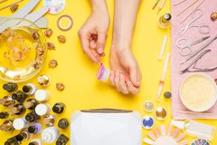 Manicure - means for creating, gel polishes, all for nail care, beauty concept, care. On a yellow background, a woman receives a. Manicure of nails. Service set stock image