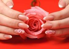 Manicure. Na czerwonym tle żeńskie ręki zdjęcia stock