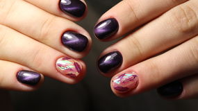 Manicure nail design cat`s eye, feathers on broken glass. Manicure nail design cat`s eye, feathers Stock Images